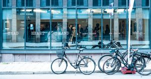 Bikes on road in front of glass building in Norway
